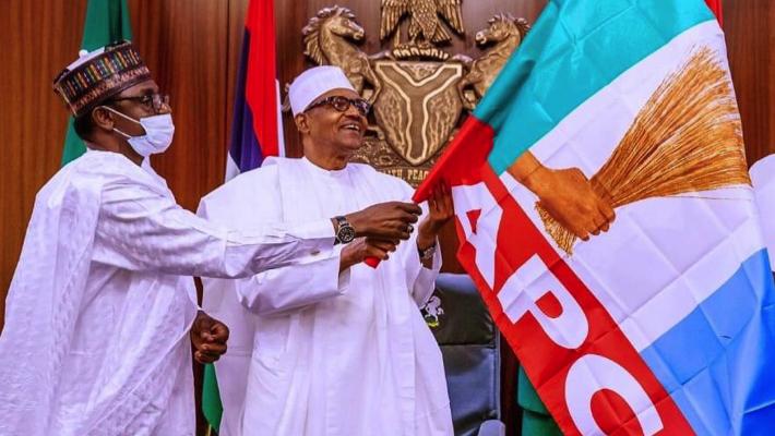 Mai Mala Buni holding APC flag with Buhari