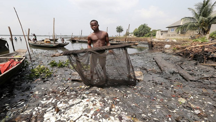 A fisherman displays his oil soaked fishing net on the polluted shoreline in Bodo